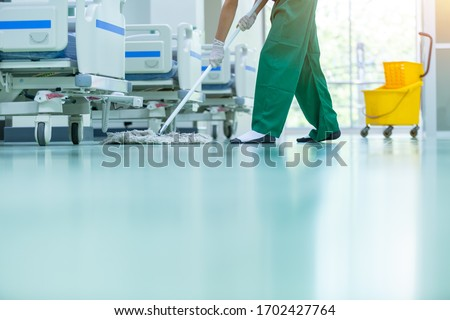 Cleaner using mops, cleaner with mop and uniform cleaning hall floor, hospital cleaning floor with mop in patient room the hospital epoxy floor. #1702427764