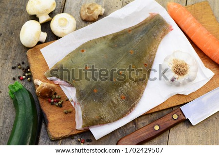 Raw fish, halibut with herbs on plate, closeup.