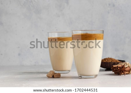 Iced Dalgona coffee in tall glass with spices. A trendy fluffy creamy whipped coffee. Korean coffee drink. Light grey concrete background.  #1702444531