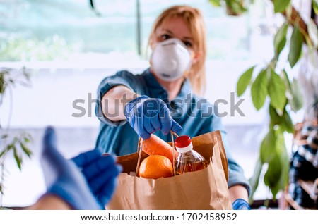 Woman delivering Food in paper bag during Covid 19 outbreak. Female  Volunteer holding groceries in the house porch. Delivery woman in face mask and gloves giving Donating neccessities to a hand Royalty-Free Stock Photo #1702458952