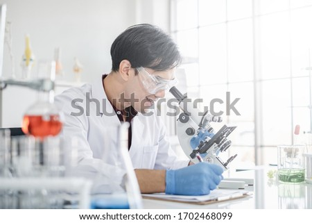 A male scientist with black hair smiling wearing white coat and protective glassware writing and looking into a microscope in a laboratory setting with test tubes. #1702468099