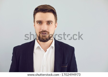 Puzzled insecure man in casual jacket on a gray background. Expression of emotion #1702494973
