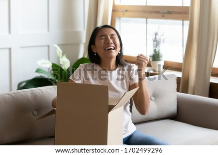 Asian woman sitting on sofa opens delivered parcel feels overjoyed. Excited girl customer unbox cardboard box at home satisfied with great purchase by trusted postal shipping delivery service concept #1702499296