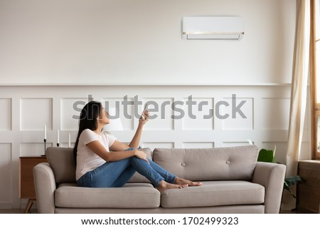 Vietnamese young woman relaxing on comfy couch in contemporary living room with air conditioner, holding remote control turning on or off cooler system, setting comfortable temperature at modern home #1702499323