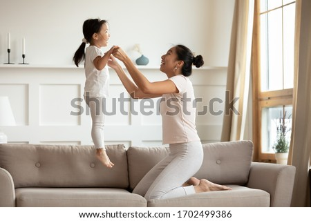Vietnamese young mother holding hands of little asian toddler lively daughter while she jumping on couch in living room. Active time with children, fun and fit, playtime with child at home concept #1702499386