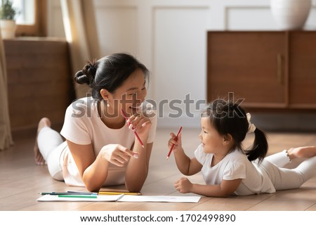 Educational pastime develop creativity skill in kid concept. Asian mother her small daughter lying on warm wooden floor in sunny cozy living room, mom teach girl paint use album and colourful pencils #1702499890
