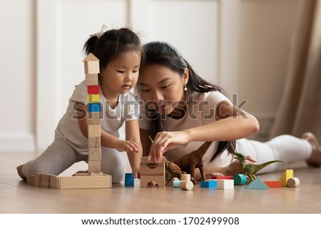 Involved little daughter her vietnamese mother play on warm floor using wooden colorful blocks create towers and buildings improve fine motor skill of kid. Funny educational games for children concept #1702499908