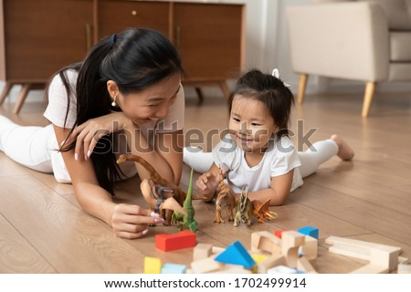 Lying on warm wooden floor asian mom play game with little daughter holds dinosaurs toys heap of colorful construction blocks nearby. Spend time have fun together educational activity with kid concept #1702499914