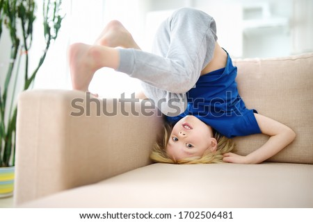 Little boy is standing on own head on sofa at home while coronavirus epidemic. Bored lonely child. Difficulties of family with preschool children during quarantine. Stay at home.