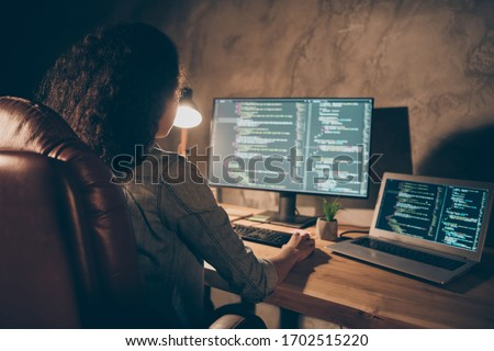 Back rear spine view photo concentrated afro american girl company administrator sit evening desk table lamp use computer work data debugging improvement binary algorithm code in workstation #1702515220