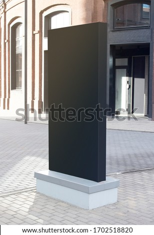 Blank black vertical pylon stand mockup brick building, side view. Empty light box or commercial tower for city information mock up. Clear media or promotion frame signage mokcup template.
