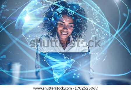 Cheerful young African American woman using laptop in blurry office with double exposure of futuristic network interface and planet hologram. Concept of internet and communication. Toned image Royalty-Free Stock Photo #1702525969