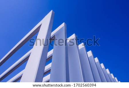The fence on the sky background against the wall And abstract architecture contrasting with the blue sky With clear and beautiful light shadows Modern concepts Royalty-Free Stock Photo #1702560394