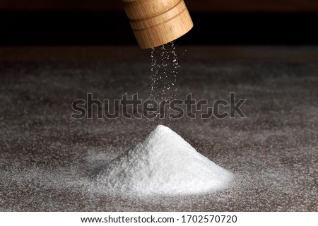 Wooden salt grinder and pile of salt. Salt falls from the grinder on a table full of salt.  Royalty-Free Stock Photo #1702570720