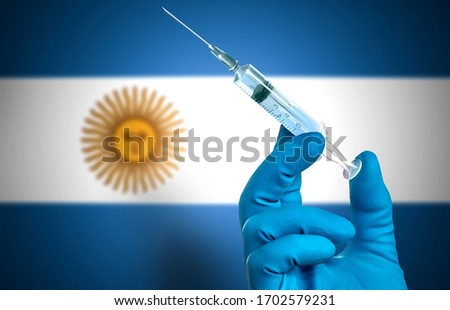 Fight against the epidemic of coronavirus in Argentina. Doctor's hand in  gloves with vaccine for the treatment of the COVID-19 on the background of the flag of Argentina  .Flu shot in Argentina #1702579231