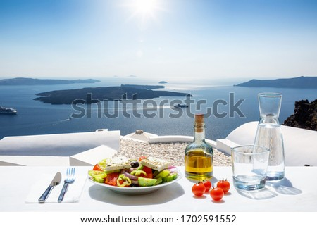 A Greek salad with olive oil and tomatoes in front of the a breathtaking view to the blue, Aegean sea as a concept of Greek food in summer time #1702591552