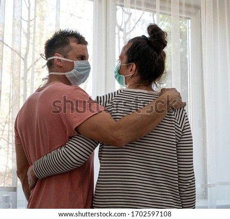 Healthcare concept. Sad couple in masks posing near window at home #1702597108