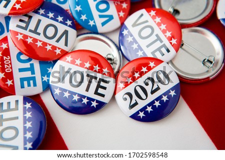 Red, white, and blue vote buttons on background with American flag, elections 2020 #1702598548