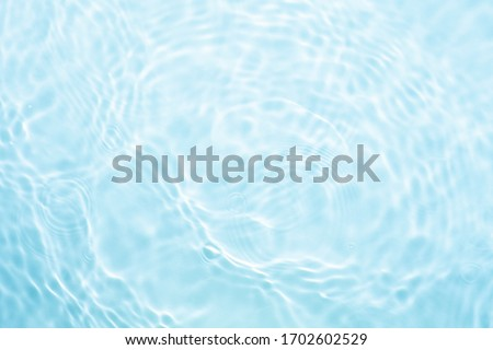 Reflections of blue water or cosmetic moisturiser toner or lotion light with scattered sun texture #1702602529
