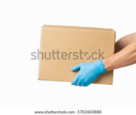 Courier presents cardboard box in rubber gloves, side view #1702603888