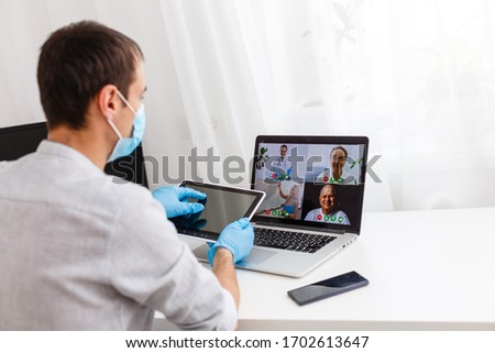 Coronavirus. Man in quarantine for coronavirus wearing protective mask, he's using the notebook. Stay at home. Working on quarantine. Protection. Health care. Video call. Video conference. #1702613647