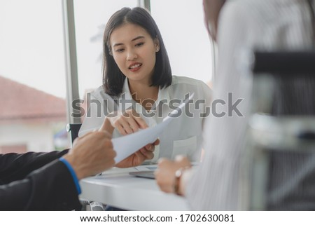 finance consultancy business concept.  Happy young female financial advisor talking to client and showing report paper of funds investment to customer. #1702630081