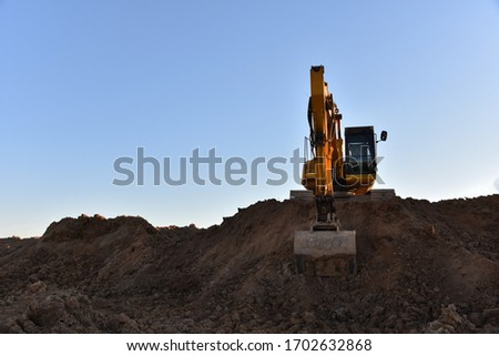 Yellow excavator during earthmoving at open pit on blue sky background. Construction machinery and earth-moving heavy equipment for excavation, loading, lifting and hauling of cargo on job sites #1702632868