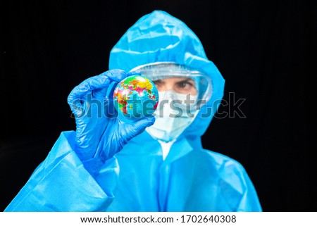 Virus. A woman in a protective antivirus suit is holding a miniature Earth placent in her hands. Royalty-Free Stock Photo #1702640308