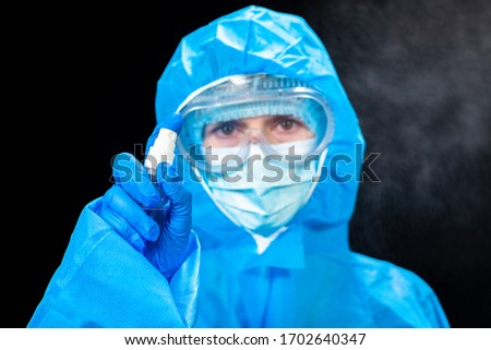 Hand disinfection. A woman in a protective antivirus suit holds a hand sanitizer in her hands. #1702640347