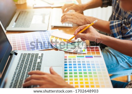 The designer works with a laptop while also designing colors for his work.