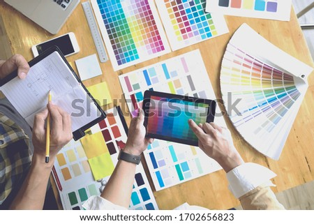 Graphic designers use the tablet to choose colors from the color bar example for design ideas, Creative designs of graphic designers concept.