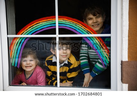 Three kids, two school kids boys and toddler girl with rainbow painted with colorful window color during pandemic coronavirus quarantine. Children painting rainbows with the words Let's all be well.