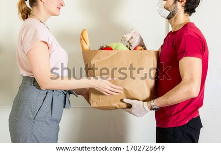 Courier in protective mask and medical gloves delivers takeaway food. Delivery service under quarantine, disease outbreak, coronavirus covid-19 pandemic  #1702728649