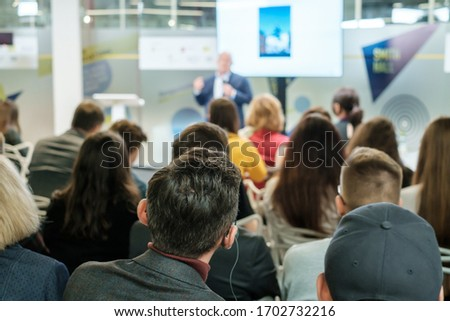 Audience listens lecturer at workshop in conference hall Royalty-Free Stock Photo #1702732216