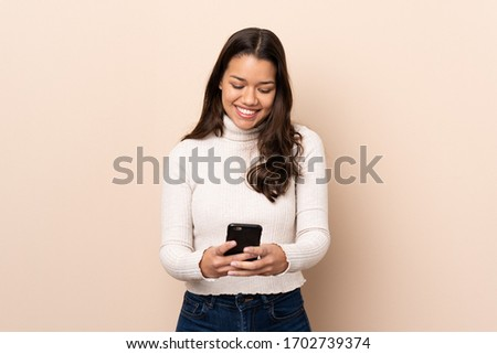 Young Colombian girl over isolated background sending a message with the mobile