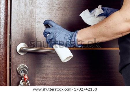 Hand in protective glove with rag cleaning door handle. Covid-19 disinfection concept Royalty-Free Stock Photo #1702742158