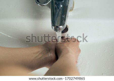 Washing hands under flowing tap water. Royalty-Free Stock Photo #1702749865