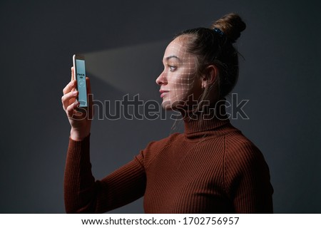 Woman scans face using facial recognition system on mobile phone for biometric identification. Future high tech technology and face id    #1702756957