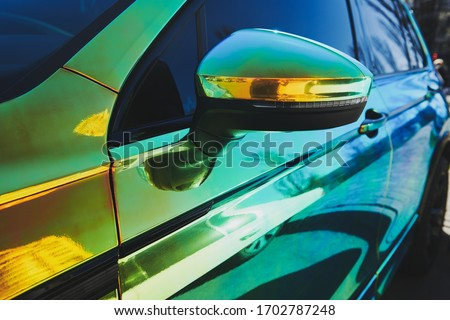 Chameleon holographic colour car. Side view. Driver's door and side mirror. closeup. Car wrapping. Car exhibition. Royalty-Free Stock Photo #1702787248