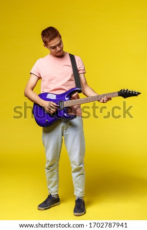 Lifestyle, leisure and youth concept. Vertical shot of creative good-looking asian man playing electric guitar, tuning in before perform on stage, look at instrument, stand yellow background #1702787941