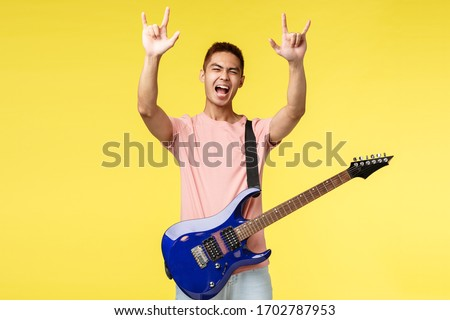 Lifestyle, leisure and youth concept. Good-looking asian guy having fun performing on stage, hold electric guitar, show rock-n-roll gesture and shouting enthusiastic, have fun, yellow background #1702787953