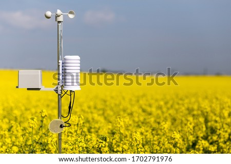Smart agriculture and smart farm technology concept. Weatherstation with anemometer, a meteorological instrument used to measure the wind speed and thermometer, measuring of rainfalll and leaf wetness Royalty-Free Stock Photo #1702791976