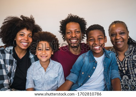 Portrait of african american multigenerational family looking at camera while sitting on sofa couch at home. Family and lifestyle concept. Royalty-Free Stock Photo #1702810786