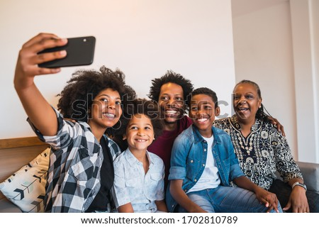 Portrait of african american multigenerational family taking a selfie together with mobile phone at home. Family and lifestyle concept. Royalty-Free Stock Photo #1702810789