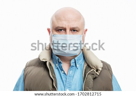 Bald adult man in a medical mask on a white background. Close-up. Precautions quarantined for the period during the coronavirus pandemic. #1702812715