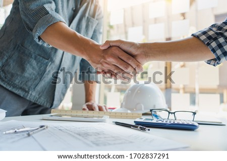 Architect and engineer construction workers shaking hands while working for teamwork and cooperation concept after finish an agreement in the office construction site, success collaboration concept Royalty-Free Stock Photo #1702837291