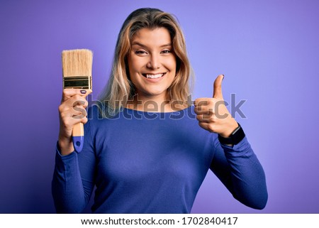 Young beautiful blonde painter woman painting using paint bush over purple background happy with big smile doing ok sign, thumb up with fingers, excellent sign