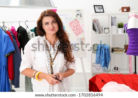 Friendly atelier worker meets customer with smile. Needlewoman in her room makes costumes. Bright workshop for tailoring costumes for childrens parties. Woman employee company animators