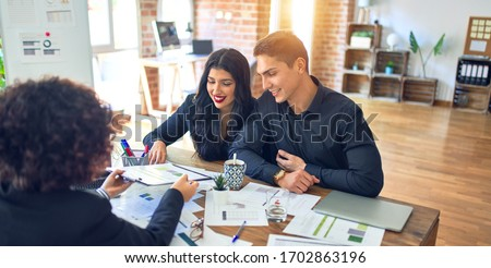 Young beautiful couple applying for mortgage. Sitting smiling happy meeting with real state agent considering mortgage loan at bank Royalty-Free Stock Photo #1702863196