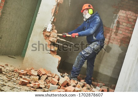 demolition work and rearrangement. worker with sledgehammer destroying wall Royalty-Free Stock Photo #1702878607